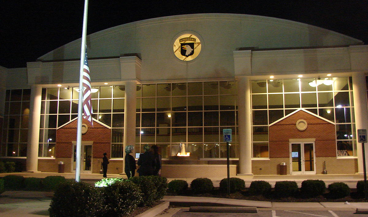 lighted building at night with american flag in front