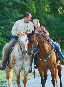 smiling man and woman riding horses together
