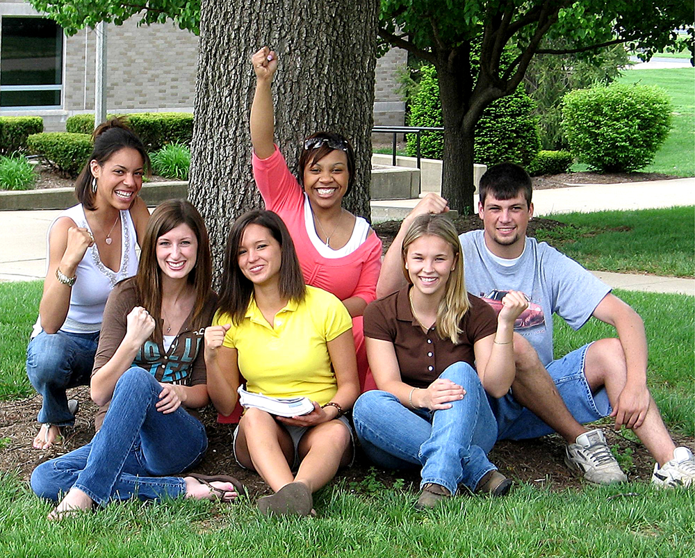 six college students sitting under tree with building in the background