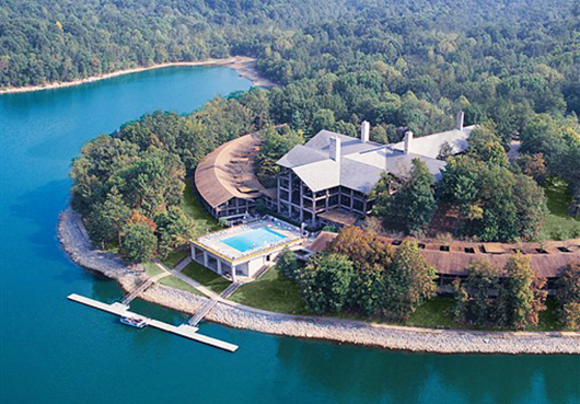aerial photo of large house on lake surrounded by woods